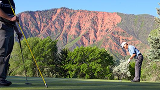 Two men golfing in the mountains